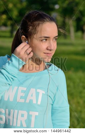 A medium closeup portrait of a young beautiful caucasian woman with a chestnut hair and green eyes placing a headphone in her ear while looking away and smiling. Green background.