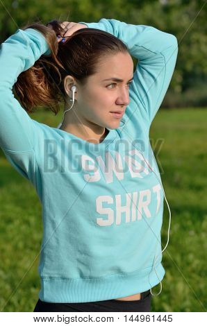 A medium closeup portrait of a young caucasian woman with green eyes fixing her hair in a ponytail while gazing away. The model is wearing a sport blue sweatshirt and black shorts. Sunset lighting.