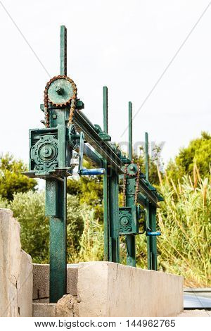 The old mechanism for shutoff of water in the channel the chain and gears with a handle.