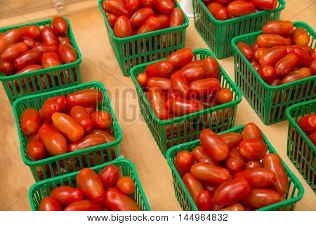 Small tomatoes on plastic tray for sale