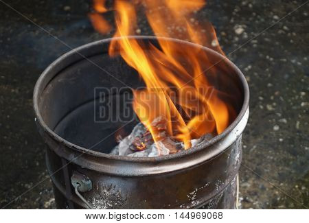 Flaming on burnt Chinese joss paper and ashes in old rusty metal tank