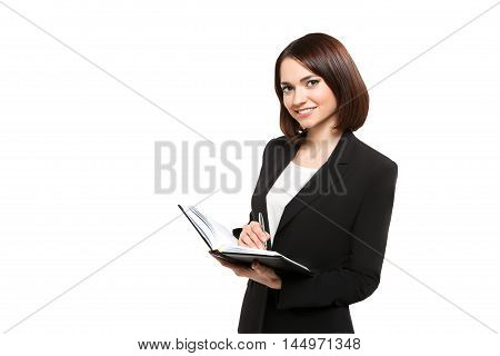 Business woman holding in hands daily, isolated on white background with clipping path. She is writing in her organizer, makes notes in notebook.