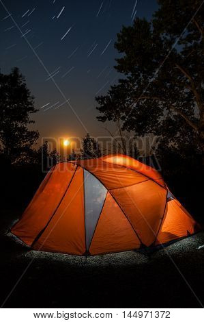 Long exposure of a camping tent at night with rising moon on horizon and star trails in the night skies.