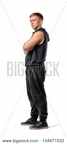 Side view of muscled young man standing with his arms folded looking at the camera, isolated on white background. Bodybuilding and self-improvement. Physical training. Beauty and strength.