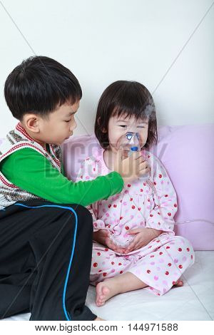 Asian Girl Having Respiratory Illness Helped By Brother With Inhaler. Happy Family Concept.