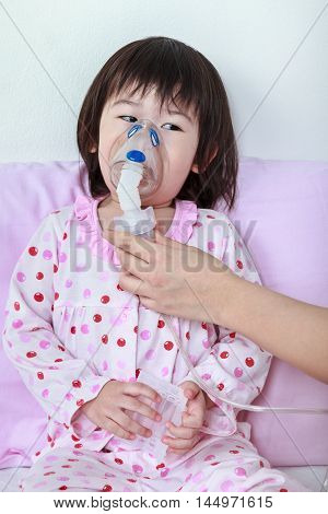 Asian Girl Having Respiratory Illness Helped By Health Professional With Inhaler.
