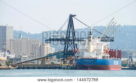 Oakland CA - August 23 2016: Bulk Carrier INSPIRATION LAKE docked at Schnitzer Steel at the Port of Oakland.Schnitzer Steel recycles scrap metal into finished steel products such as rebar and wire rod.