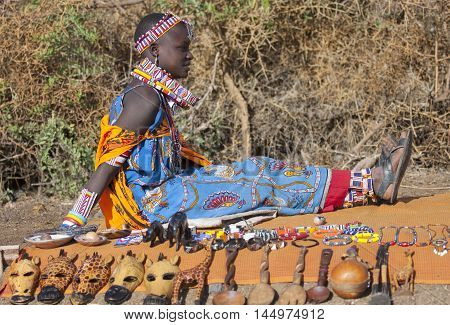 Editorial photo of a beautiful young woman of the tribe Maasai in national costume selling souvenirs Amboselli January 2009 Kenya