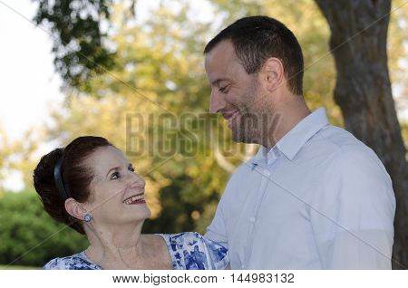 Mother and her adult son looking at each other outdoors on a fall evening cherishing the moments of life.