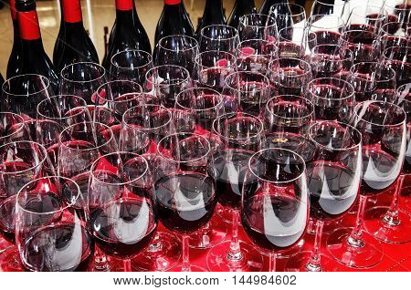 glasses and bottles of red wine on cocktail party buffet 3table