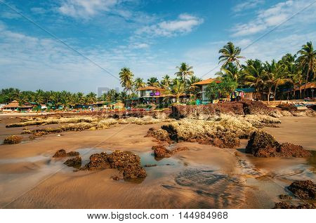 Chapora, India - Dec 6, 2014: Guesthouses and sunbeds on the shore of the Arabian Sea in the middle of rocks and sandstone in Ashvem Goa India