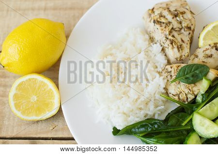 Chicken breasts baked with thyme and lemon and served on a white classic plate together with white rice cucumber slices and baby spinach leaves