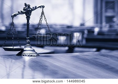 Symbol of law and justice in the empty courtroom law and justice concept blue toned.