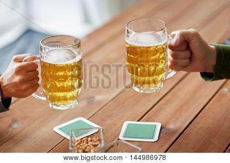 people, leisure and drinks concept - close up of male hands with beer mugs and peanuts at bar or pub poster