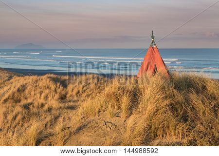 Tepee on a beach sand dune with earnly morning sunlight.