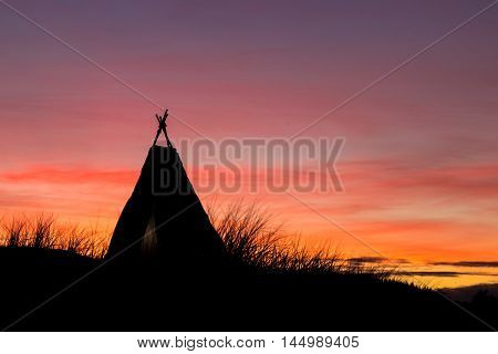 Tepee on a hill with a wonderful dawn sky behind it.