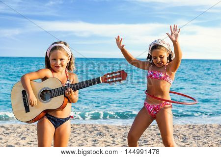 Close up portrait of two little girls in swimwear dancing and singing with guitar on beach.