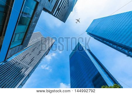 Skyscrapers with a flying airplane against blue sky.