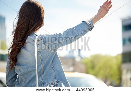 gesture, hitch-hike, travel, tourism and people concept - young woman or teenage girl catching taxi on city street or hitch-hiking