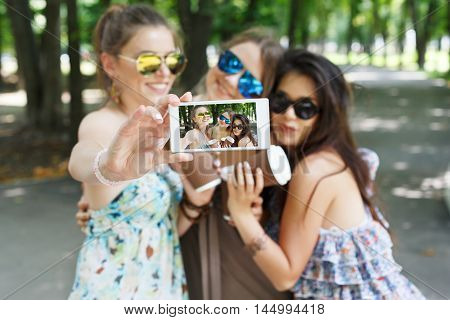 Three girls friends with coffee take away outdoors and someone POV view, taking photos at digital camera of smartphone. Young females at mobile screen, having fun in summer park. Lifestyle portrait.