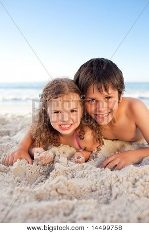 Little boy and his sister lying down on the beach poster