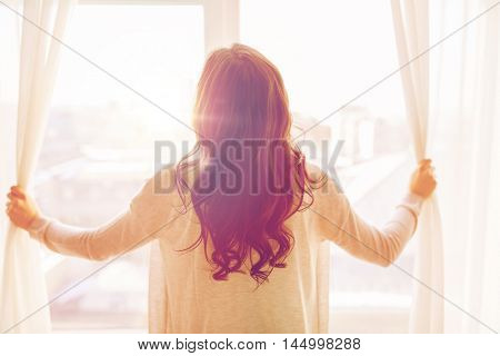 people and hope concept - close up of happy woman opening window curtains