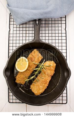grilled scottish kipper with oat bran slice lemon rosemary in a cast iron pan