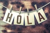 "The word ""HOLA"" stamped on cards and pinned to an old piece of twine over a rusted metal background. poster"