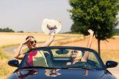 Best friends having summer joyride in convertible car passing a field  poster