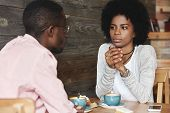 Close up portrait of African American friends at cafe having serious conversation fashionable hipster woman with Afro hairstyle looking at her boyfriend with puzzled and thoughtful face expression poster