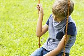 sad lonely boy sitting on swings at outdoor playground. Close up. Sad lonely depressed unhappy mood poster