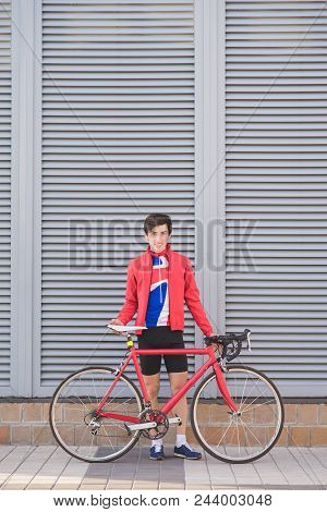 Portrait Of A Cyclist Athlete Standing Against A Gray Wall With A Red Road Bike. Portrait Of A Cycli