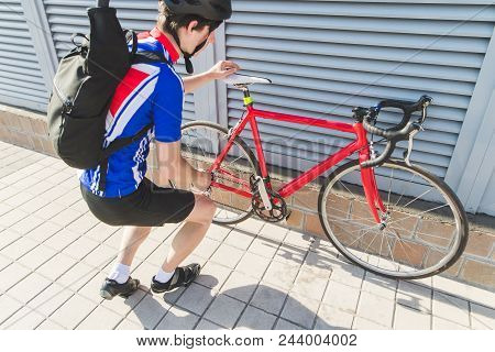 Athlete Cyclist Checks The Bicycle's Performance On The Street Under A Gray Wall. Bicycle Repair On