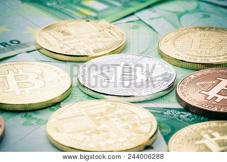 Studio Shot Of Different Bitcoin Physical Golden Coins On 100 Euro Bills Banknotes. Bitcoin Is A Blo