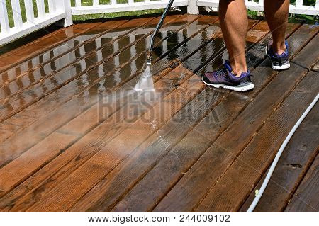 A Sprayer Using Water Pressure Cleans The Grime, Dirt, And Algae Off Of A Redwood Deck.