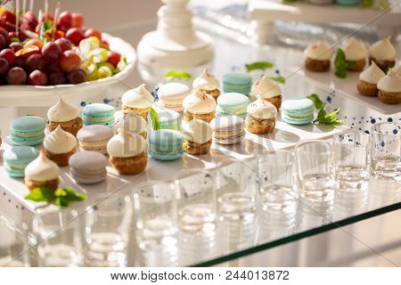 Delicious Macaroons And Cupcakes On Table At Wedding Reception. Candy Bar. Tasty Colorful Sweets For