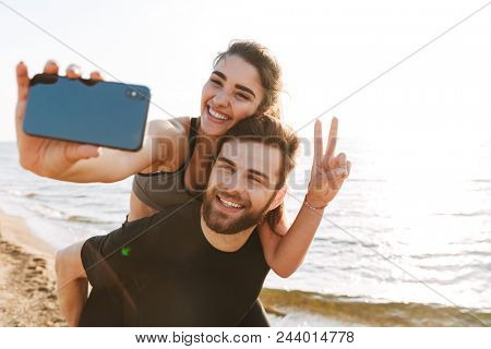 Happy young man carrying his girlfriend on his back while she is taking a selfie at the beach