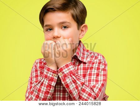 Handsome toddler child with green eyes terrified and nervous expressing anxiety and panic gesture, overwhelmed over yellow background