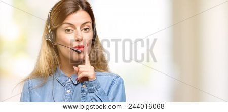 Consultant of call center woman in headphones with index finger on lips, ask to be quiet. Silence and secret concept