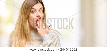Young beautiful woman covers mouth in shock, looks shy, expressing silence and mistake concepts, scared