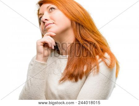 Beautiful young redhead woman thinking and looking up expressing doubt and wonder isolated over white background