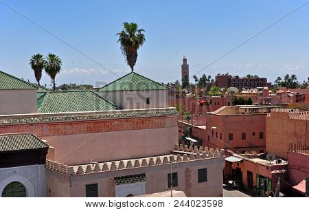 Historic Moroccan City Of Marrakech With Mosque, Flying Birds And The High Atlas Mountains In The Ba