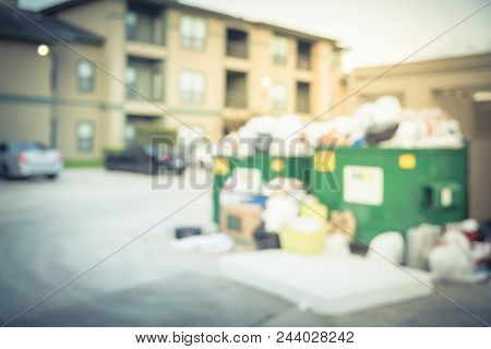 Abstract Blurred Overflowing Dumpster At Apartment Building In Usa