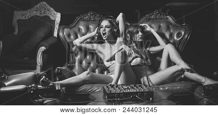 Two Sexy Young Glamour Dj Girls With Bright Make-up In Underwear And Headphones Sitting On Brown Lea