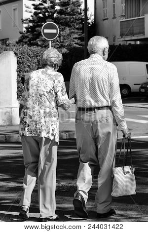 Photo Back View Of Well-dressed Silver-haired Senior Couple Aged Man And Woman Walking Arm-in-arm In