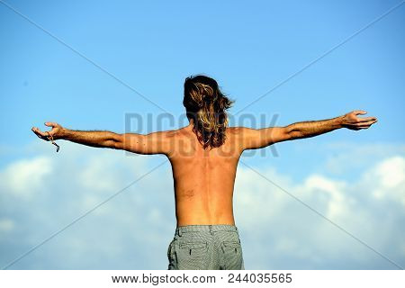 A Thoughtful Moment: A Topless Male With Outstretched Arms Standing Against A Blue Sky And Clouds On