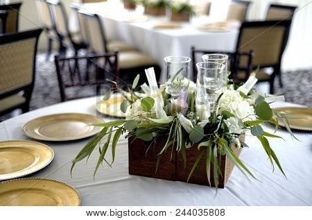 Floral Arrangement Sitting On A White Table Cloth On A Reception Table Surrounded By Gold Plates Awa