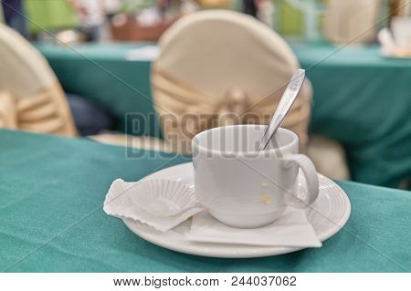 Empty Unclean White Cup Of Coffee With Spoon In Conference
