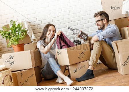 Casual Happy Couple Unpacking Carton Boxes With Home Stuff Sitting On Floor Of New Home.
