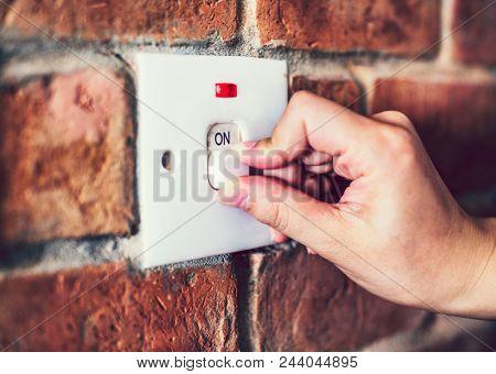 A light switch on a brick wall